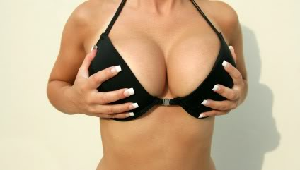 a woman holds her huge breast implants