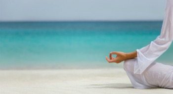 close-up on woman practicing yoga on tropical beach in the Caribbean